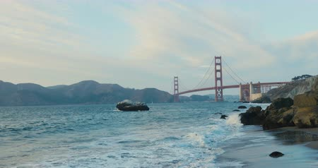 Beautiful sunset at the golden gate bridge in san francisco from baker beach view. Waves clashing at the clifs.