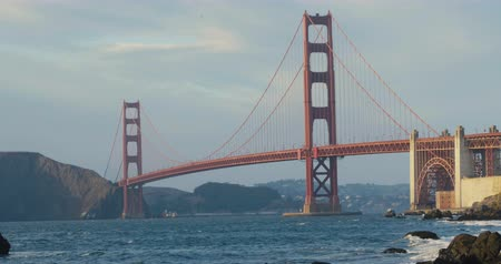 piekarz : Beautiful sunset at the golden gate bridge in san francisco from baker beach view. Waves clashing at the clifs.