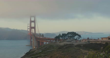 Golden Gate Bridge sunset with fog and cars passing by during rush hour wide shot Wideo