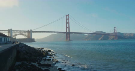 Golden Gate Bridge from Bellow by the presidio, sunset sky and waves clashing by the shore Wideo
