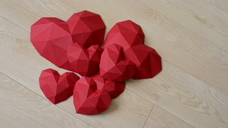 fa háttér : Heap of red polygonal paper heart shapes on wooden background, top view, rotating video Stock mozgókép