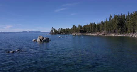 springtime : Flying over the surface of Lake Tahoe with boulders in water Stock Footage
