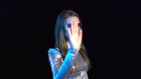 ezüst : Cyber young woman in silver clothing wearing eyeglasses turning over the virtual pages, over dark background