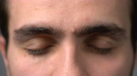 kinyit : Zoom in video of closeup front view of young man opening his eyes and looking at camera