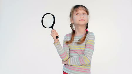 növelni : Little girl standing with magnifying glass, locked down real time video