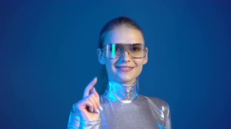 presleme : Young woman in silver clothing wearing eyeglasses pressing virtual buttons, over blue background