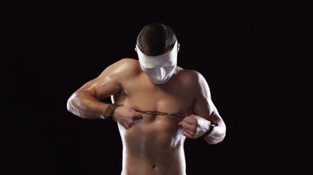 restraining : Strong athletic man with muscular torso wearing white mask with hands in handcuffs tied breaking chain