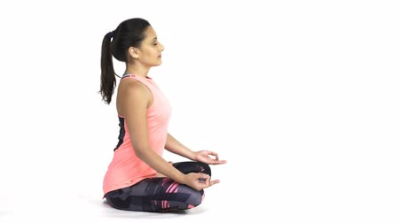 za : Young attractive woman practicing yoga, doing Padmasana, lotus pose in full length, side view, isolated over white studio background