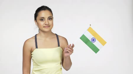 cope space : Young female standing smiling at camera holding national flag of India, over white background