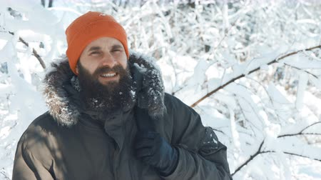 approving : Closeup of a bearded man smiling at camera outdoors in a winter snowy day and gesturing thumb up