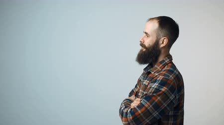 dobrado : Closeup profile of confident hipster bearded man standing with folded hands looking forward isolated on gray background, turning to camera and gesturing thumb up Vídeos