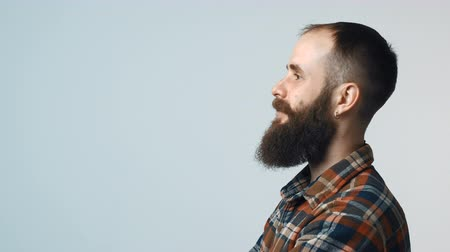 clasped : Closeup profile of confident hipster bearded man standing with folded hands looking forward isolated on gray background