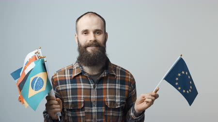 глобализация : Closeup of bearded man standing looking at camera holding a bundle of national flags in one hand, and flag of European Union in another