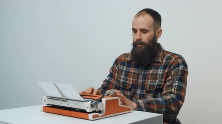 conta : Hipster sitting at table and typing with a red vintage typewriter