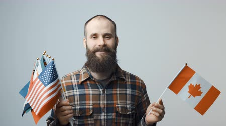 separado : Closeup of bearded man standing looking at camera holding a bundle of national flags in one hand, and flag of Canada in another