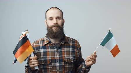 separado : Closeup of bearded man standing looking at camera holding a bundle of national flags in one hand, and flag of Ireland in another