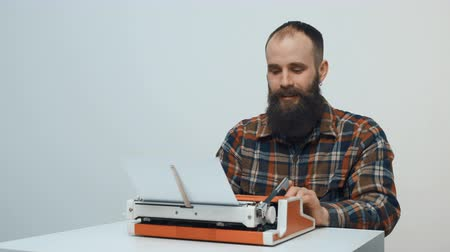 máquina de escrever : Hipster sitting at table and typing with a red vintage typewriter thinking and pointing a finger up hitting an idea Stock Footage