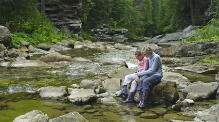 řev : Woman and little girl sitting on rocks at mountain river in canyon in summer