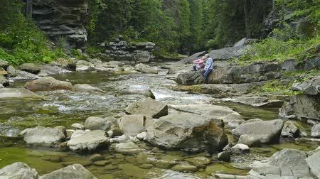 kükreme : Woman and little girl sitting on rocks at mountain river in canyon in summer