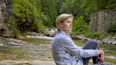 řev : Woman sitting near mountain river in canyon in summer Dostupné videozáznamy