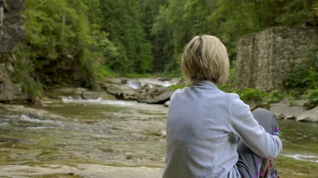 řev : Back view of a woman sitting near mountain river in canyon in summer