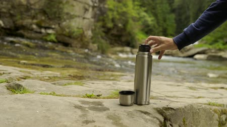 szigetelt : Man hand pouring hot drink into a mug from the thermos, in the nature park, forest and mountain river at background Stock mozgókép