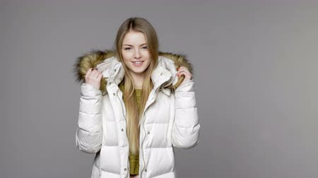 imaginário : Blond woman wearing warm winter coat with fur hood smiling at camera and blowing a kiss Stock Footage