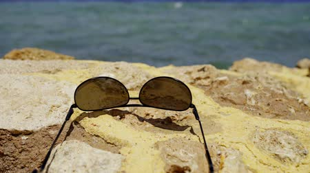 Sunglasses lying on stone fence on beach