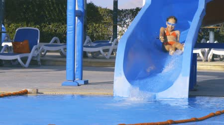 Slow motion video of a happy little caucasian girl on waterslide in aqua park pipe