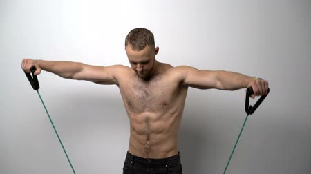 Slow motion video of a shirtless muscular man training with Resistance Band