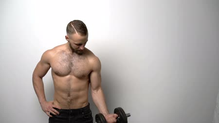üstsüz : Slow motion video of a shirtless muscular man training biceps with dumbbell Stok Video