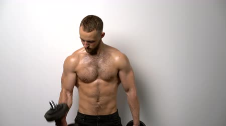 üstsüz : Shirtless muscular man training biceps with dumbbells
