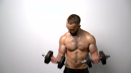 Shirtless muscular man training biceps with dumbbells