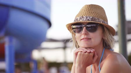 Woman in swimwear, straw hat and sunglasses sitting by swimming pool looking at camera smiling Стоковые видеозаписи