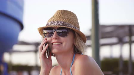 Woman in swimwear, straw hat and sunglasses sitting by swimming pool talking on phone