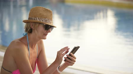 Woman in swimwear, straw hat and sunglasses sitting by swimming pool using surfing on smart phone
