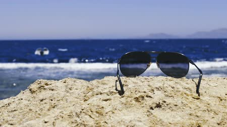 Sunglasses lying on stone on beach, focus on glasses