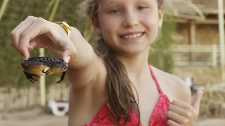 Happy girl holding showing a crab on a beach, focus on crab Стоковые видеозаписи