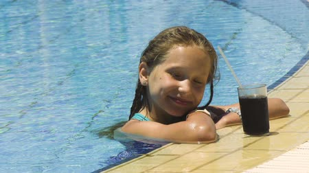 Little girl in swimming pool with cold drink looking at camera smiling, closeup