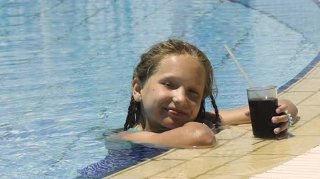 Little girl in swimming pool with cold drink looking at camera smiling and gesturing thumb up, closeup portrait