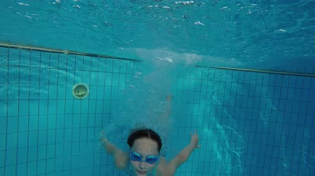Underwater video of a girl jumping in swimming pool wearing goggles Стоковые видеозаписи