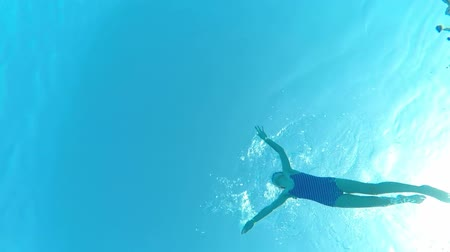 plunging : Underwater view of a little girl swimming in pool, view from below Stock Footage