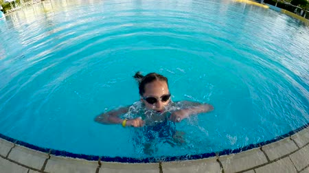submerge : Little girl in goggles jumping playing in pool gesturing thumb up and thumb down