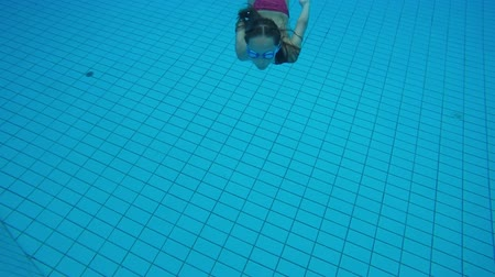 submerge : Underwater view of a little girl diving into swimming pool and swimming to the camera closeup Stock Footage