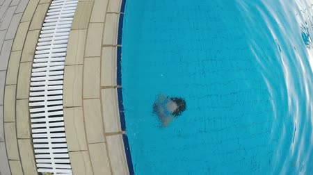 Slow motion video top view of little girl emerging from the swimming pool, gesturing double thumb up and smiling at camera Стоковые видеозаписи