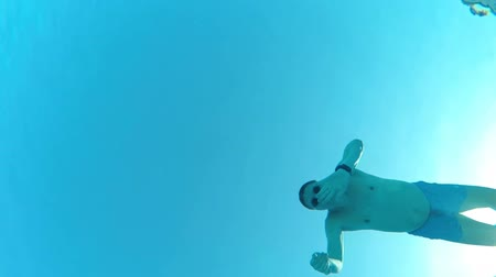 Underwater view of a male swimming in pool and waving his hand at camera, view from below Стоковые видеозаписи
