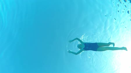 Underwater view of a little girl swimming in pool, view from below Стоковые видеозаписи