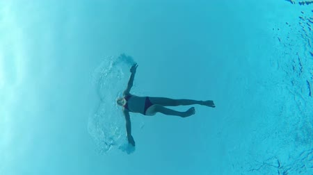 Underwater view of a little girl diving into pool, view from below
