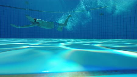 Underwater view of a male jumping and diving into swimming pool gesturing thumb up at camera, view from bottom