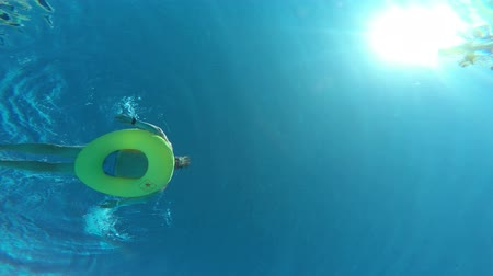 A man floating on inflatable ring in swimming pool, view from underwater from the bottom Стоковые видеозаписи